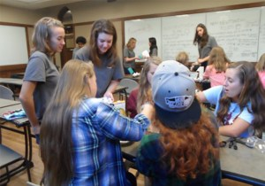 "UT engineering students (in gray shirts) help area middle and high school students during 2015's ""Tomorrow's Engineers Today"" event. UT's chapter of the Society of Women Engineers (SWE) helps stage the event, with backing from Eastman."