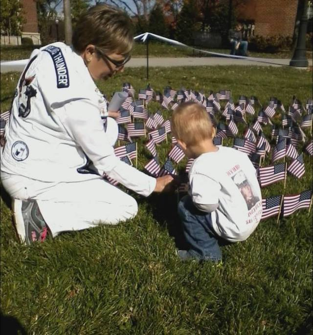 Bernice Koprince and grandson, Billy (named after William Koprince) plant flags at a veterans memorial celebration.