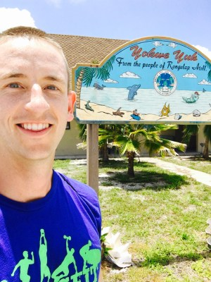 UT nuclear engineering doctoral student Adam Stratz poses in front of a welcome sign on Rongelap Atoll.