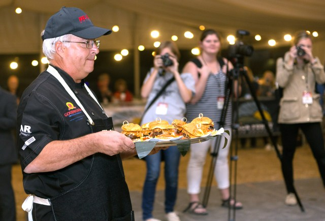 Journalism students photograph contestants bringing food to the judges' table during the burger competition at the World Food Championships.