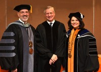 Pulitzer Prize winner and honorary degree recipient John Meacham, center, poses with UT President Joe DiPietro and Chancellor Beverly Davenport during fall commencement ceremonies at Thompson Boling Arena on December 15, 2017.