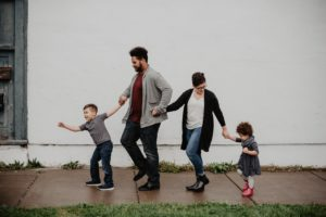 a family holds hands while walking on a sidewalk
