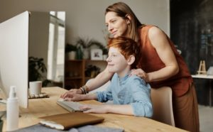 a mother helps her son on a computer