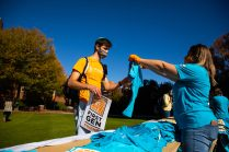 Student receiving a free t-shirt at First-Gen Week Celebration