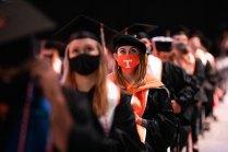 A graduate in a Power T orange face mask