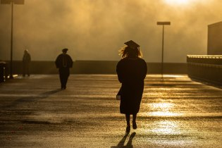 A graduate walking out of Thompson-Boling Arena on a foggy morning