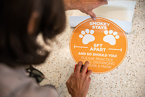 Facilities Services install COVID signage stickers on the ground inside of a Student Union entrance.
