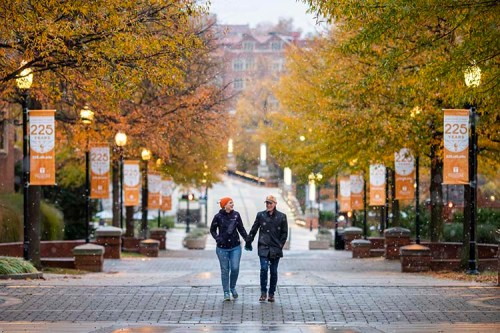 Snow flurries fall around campus as couple walks along Ped walkway