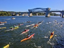 Kayakers create waves in Chattanooga water.