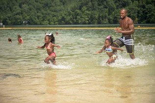 father and daughters playing in swim beach at Concord Park