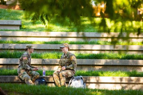 Two ROTC students laugh while visiting at the HSS Amphitheater