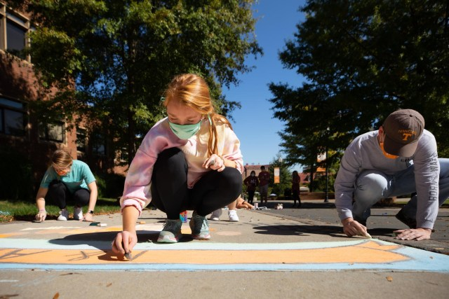 Students create chalk artwork along Ped walkway during homecoming week