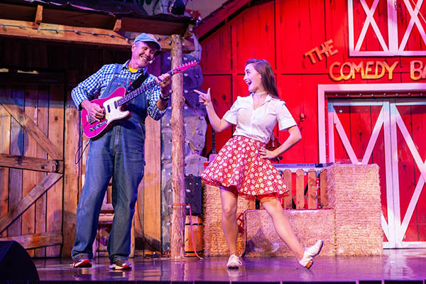 Paige Clark, right, on stage during a performance at The Comedy Barn.