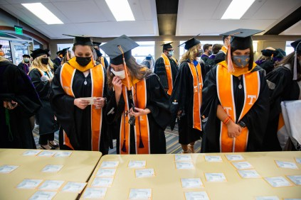 Graduates pick out their name cards at Neyland Stadium.