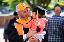 A graduate hold his daughter while she tries on his cap.