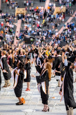Graduates toss their hats in the air in celebration at the conclusion of commencement.