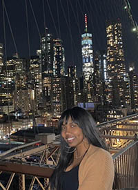 Darden poses on a bridge with the New York City skyline behind her