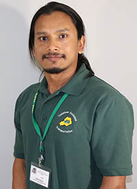 Bikash Bogati stands for a headshot in his Volunteer Assisted Transportation polo