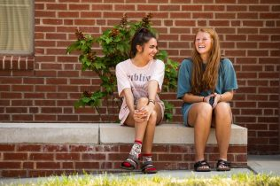 Two students connect outdoors during move-in.