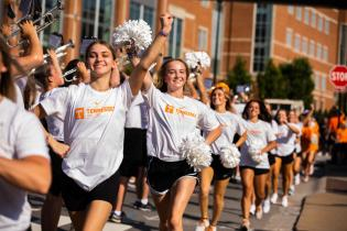 The dance team runs by the Pride of the Southland Marching Band during their game day practice performance