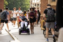 Student using a wheelchair goes to class with a friend.
