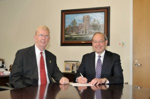 Pellissippi Community College President Allen Edwards, left, and UT Knoxville Chancellor Jimmy G. Cheek sign the formal agreement creating the bridge program.
