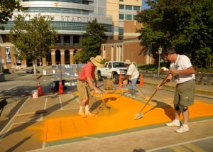 Workers painting the Big Orange T on Peyton Manning Pass