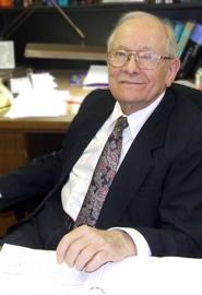 George K. Schweitzer at his desk
