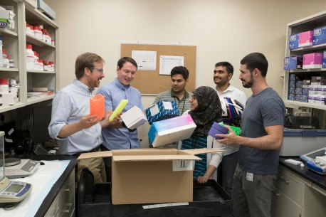 Greg Medlock, second from left with other members of Dr. Sean Moore's lab, is determining how to grow microbes most efficiently. He compared it to figuring out how to best fit many items in a box.