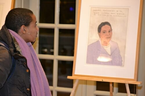 Photo: Unidentified person looking at picture on easel