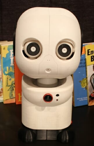Photo: Closeup of robot in front of several books