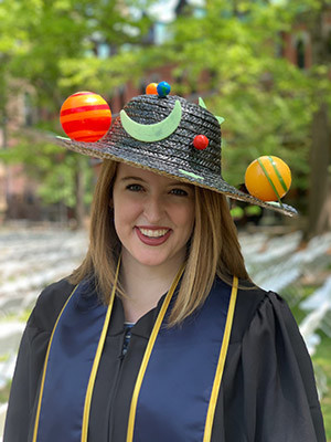 Katie Melbourne wearing a straw hat adorned with planets.