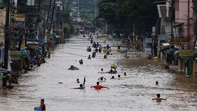 a flooded stdown in MResidents negotiate reet as it slowly inches arikina City, east of Manila. Picture