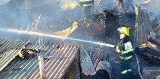 EMS workers are seen at the site of an informal settlement during fire.