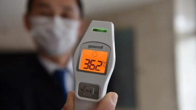 A hotel employee shows a temperature reading as he stands by the entrance to check all guests and anyone who enters the building to check for signs of the virus in the city of Wuhan