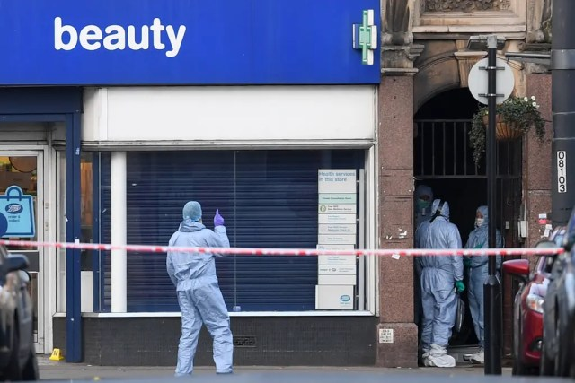 Police forensic officers work outside a store after a man was shot dead by police following reports he had stabbed two people