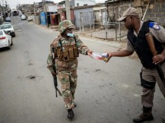 A South African soldier (left) hands over cigarettes he seized from a small shop to a policeman