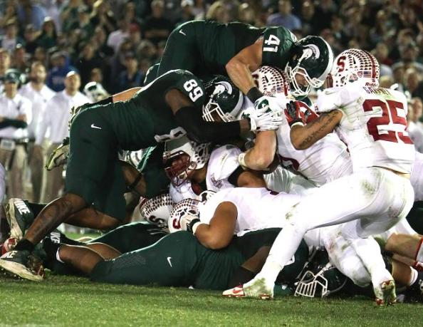 Play of the game: Michigan State lineback Kyler Elsworth goes airborne to stuff Ryan Hewitt of Stanford. Photo Credit: Jevone Moore/Full Image 360
