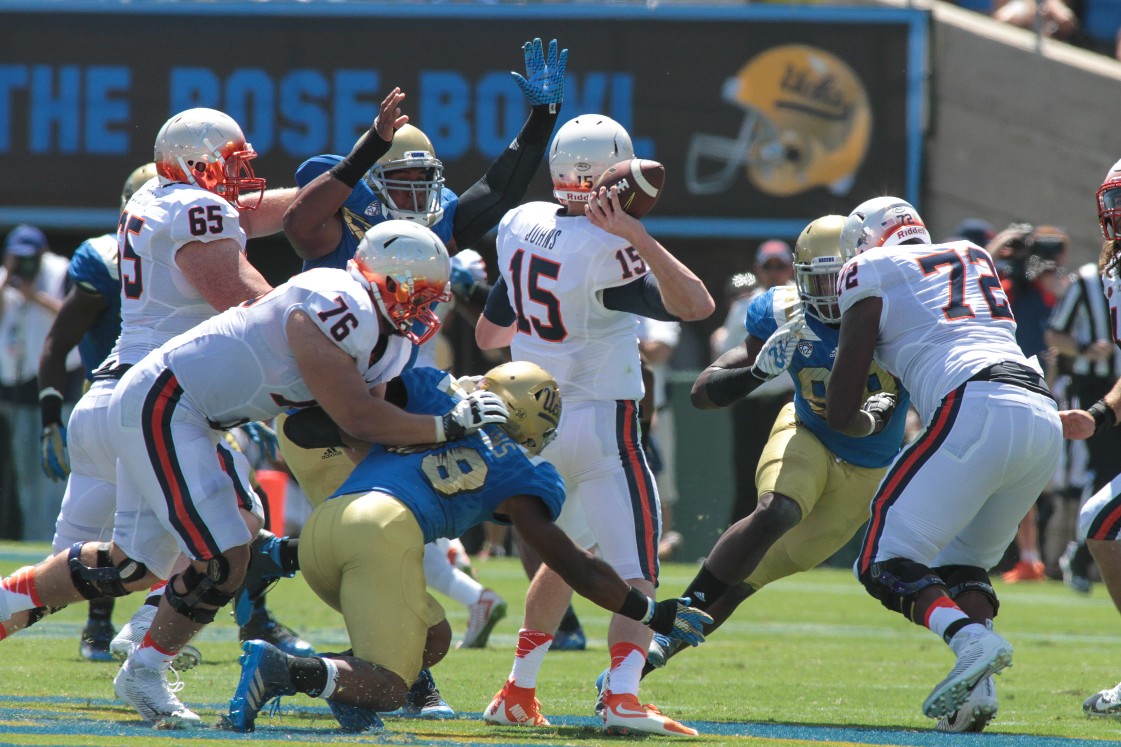 Virgina Cavalier Quarterback Matt Johns under pressure by Bruins. Photo by Jevone Moore