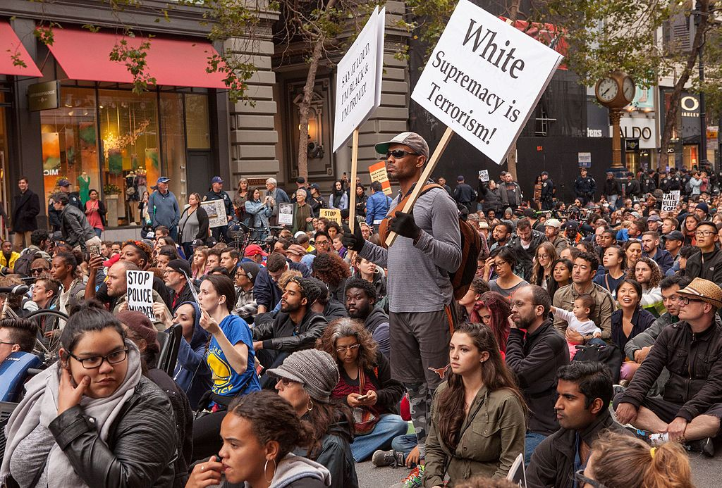 "Marchers sit on Market Street in Union Square, San Francisco, during a rally against police violence. One person standing holds signs reading ""Say It Loud, I'm Black & Proud!"" and ""White Supremacy Is Terrorism!""Photo Credit: Pax Ahimsa Gethen/Wikipedia Commons"