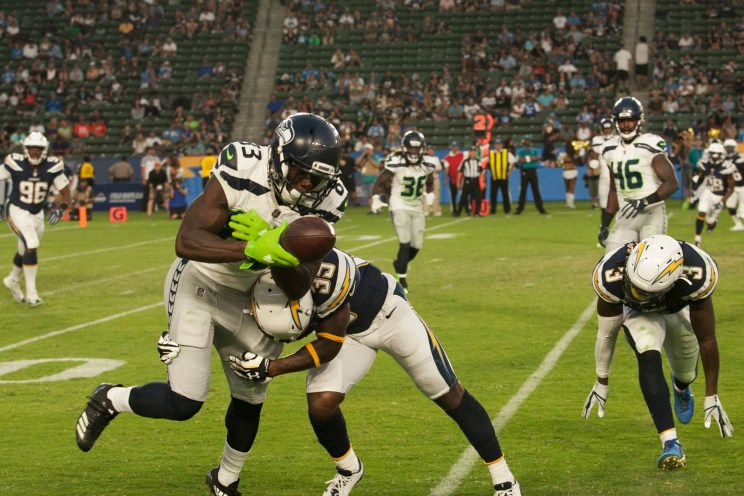 A Los Angeles Chargers defender puts the big hit on a Seattle Seahawks wide receiver in preseason action. Photo by Astrud Reed/News4usonline