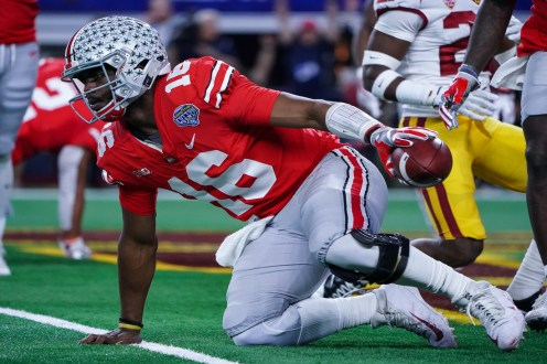 Ohio State quarterback J.T. Barrett (16) gets up off the ground after taking a big hit from the USC Trojans during the 82nd Annual Goodyear Cotton Bowl Classic. The Buckeyes defeated the Trojans, 24-7. Photo by Michael Lark for News4usonline