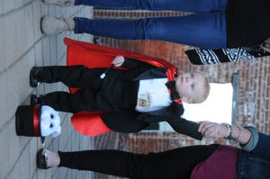 A baby in a cape and top hat at Chili Cook Off