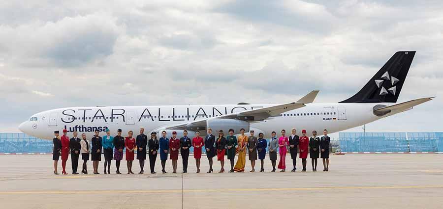 Hospedeiros de várias companhias em linha para foto. Avião da Star Alliance 20 anos por trás