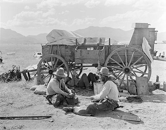 cowboys sitting next to chuck wagon