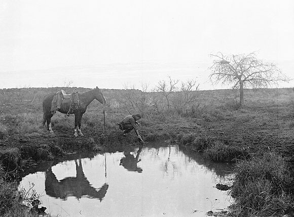 Reflection of horse and cowboy in pond