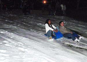 Two students enjoy sledding down the hill at Scripps Lawn.