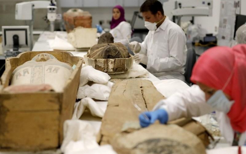Egyptian archaeologists restore the coffin and mummy of King Tutankhamun