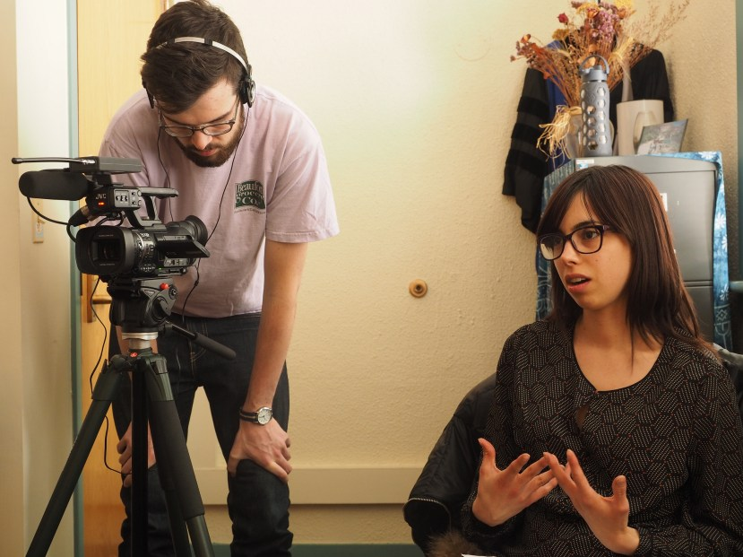 Graduate student Ted Phillips monitors the camera while fellow graduate student Natalia Bayona conducts an interview with Professor Janice Peck on Wednesday, March 4, 2015. (Photo/Roxann Elliott)