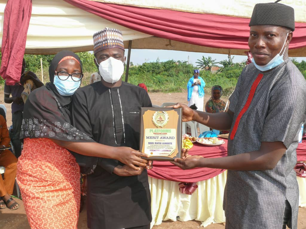 Ajakaye (middle) supported by wife, Olasumbo, receives the Award Plaque from Phamacist Olayiwola during the first Walimot-ul-Qur'an and Prize-Giving Day of Platforms Montessori School, Ota